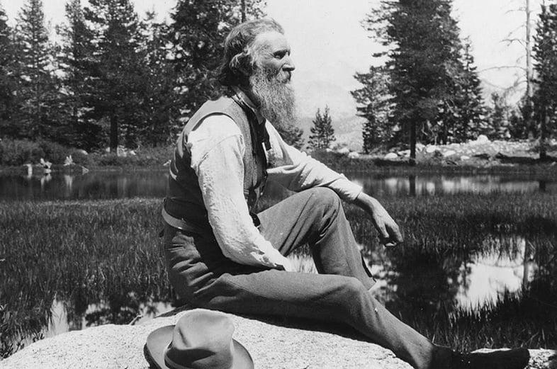 Джон Мьюир сидит на камне у озера в 1902 году.