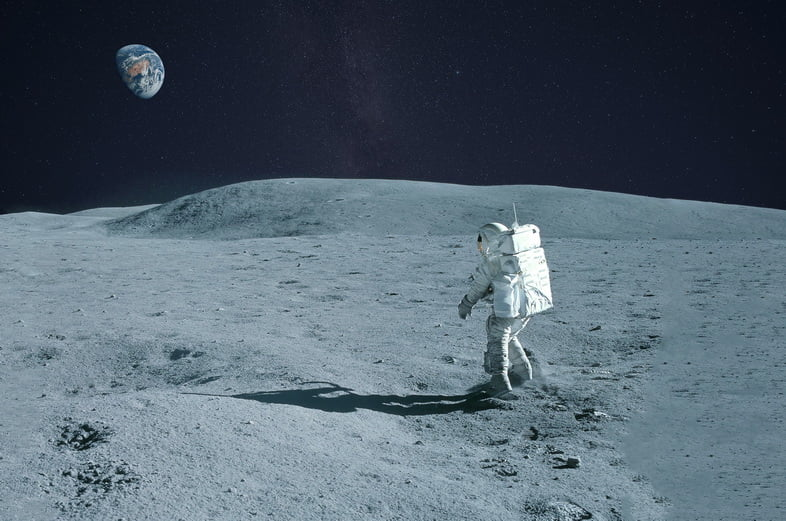 Астронавт идет по лунной поверхности с Землей на горизонте