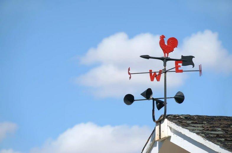 Флюгер и анемометр на фоне голубого неба.