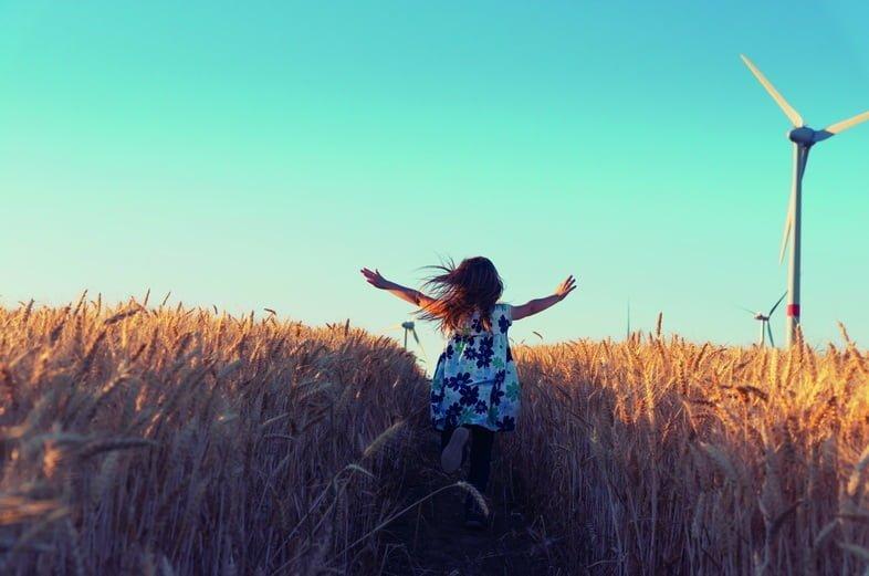 Девочка бежит по полю пшеницы с ветряными турбинами