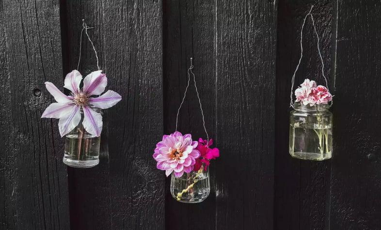 Три цветочных украшения из старых материалов, висящие на стене