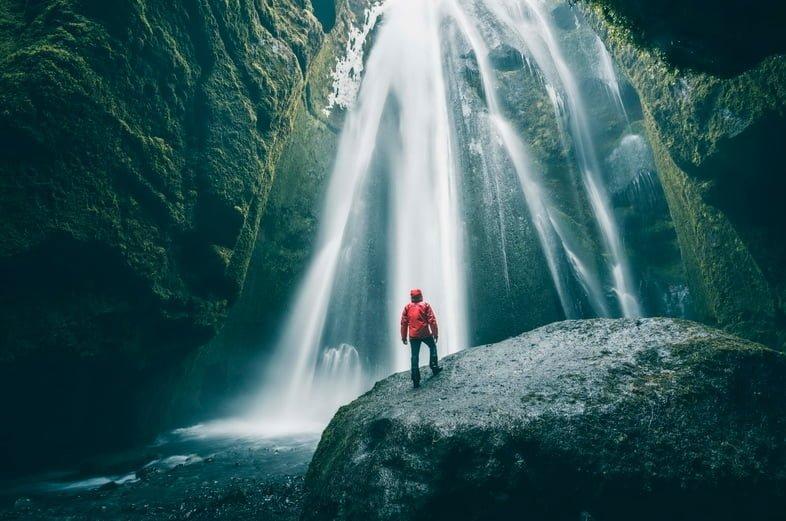Турист на скале любуется водопадом Глюфрабуй, Исландия