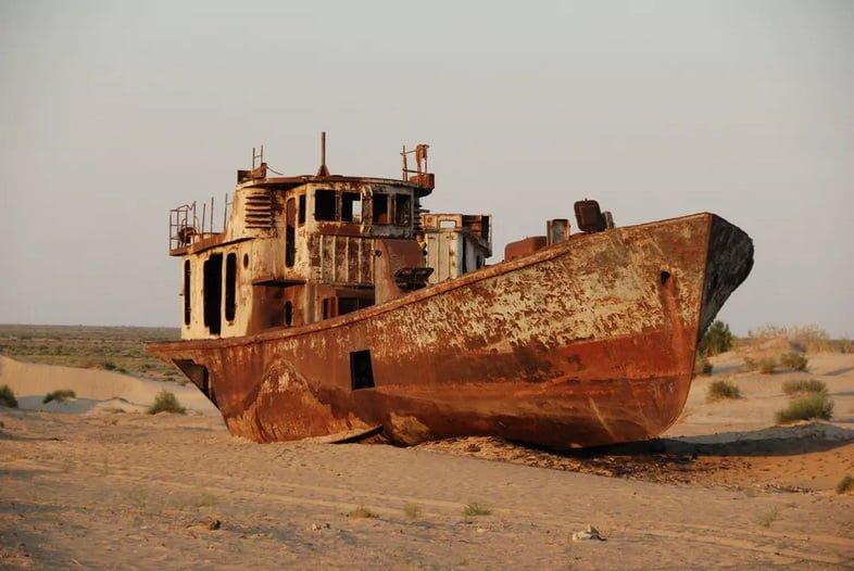 Ржавый, заброшенный корабль в песчаной пустыне, которая когда-то была озером
