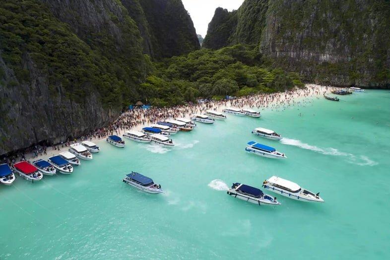 Лодки и туристы стекаются в залив Майя в Таиланде