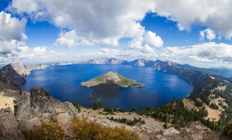 Чистое голубое озеро с островом, окруженным горами и деревьями.