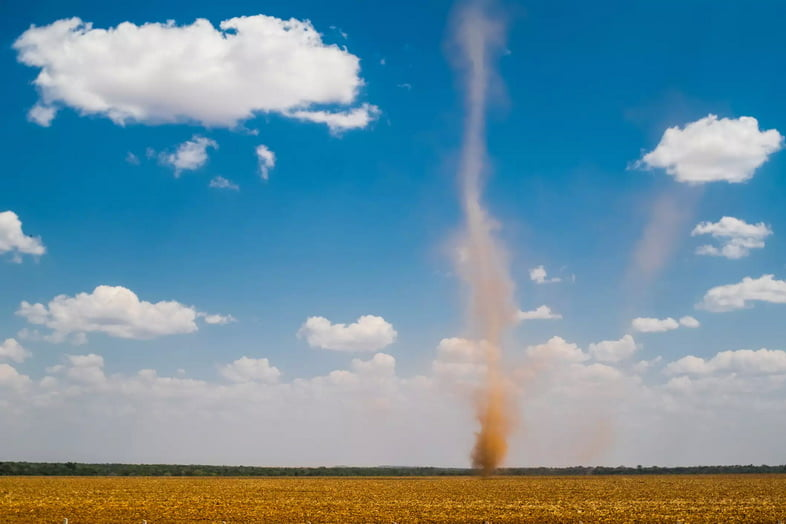 Пыльный вихрь кружит по полю в ясный день