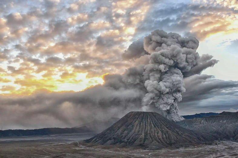 Облако пепла поднимается из вулкана на рассвете
