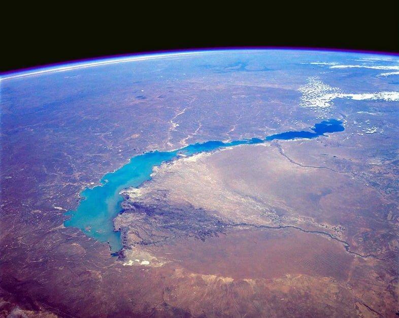 Вид под очень большим углом на длинное узкое озеро и кривизну Земли.