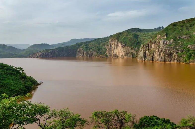 Красновато-коричневое озеро, окруженное скалами и деревьями.