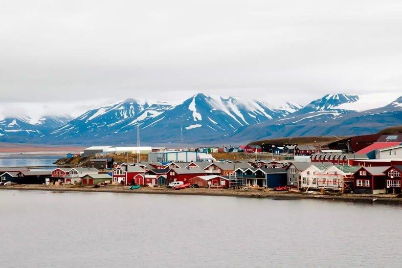 Красочная деревня и заснеженные горы у моря