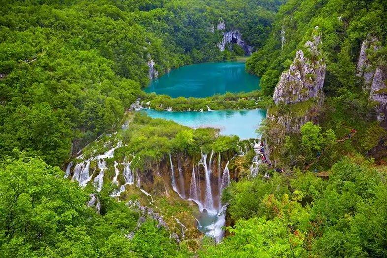 Бирюзово-голубое озеро с водопадами в лесу