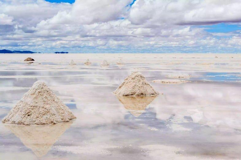 Треугольные соляные груды и облака, отражающиеся на Салар де Уюни