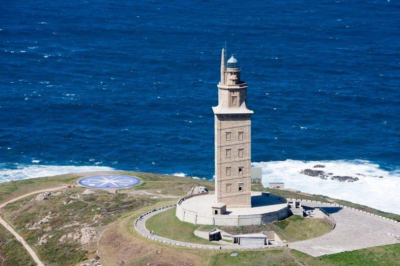 Башня Геркулеса с ярко-голубой водой позади нее.