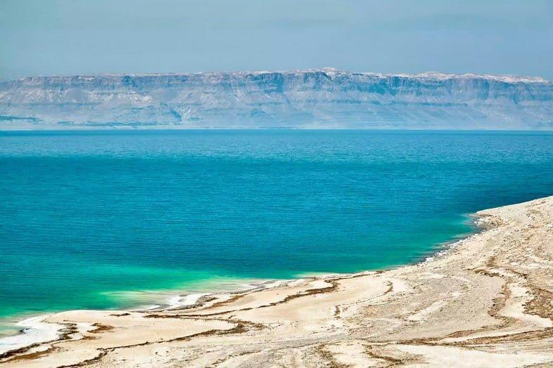 Сияющее голубое озеро с отложениями белой соли на песчаном берегу.