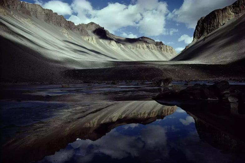 Серые скалистые горы отражаются в водах небольшого озера
