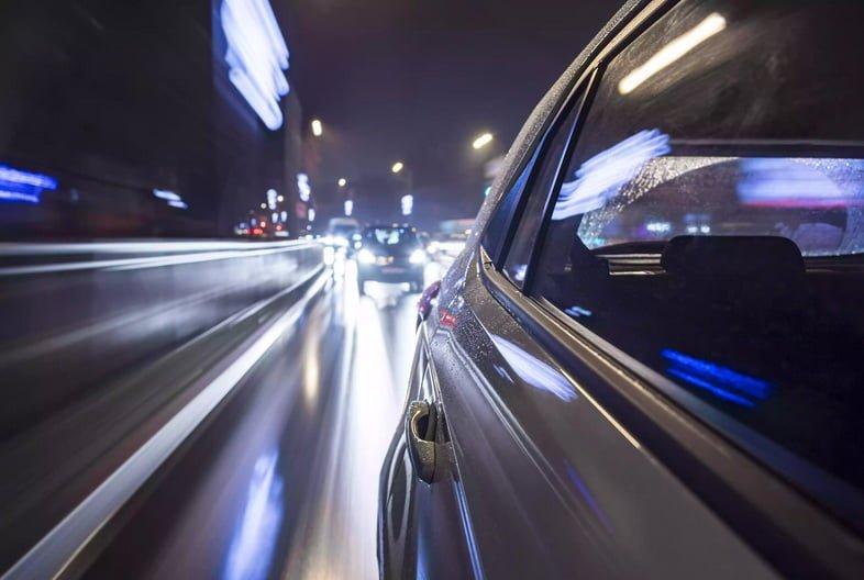 Белый электромобиль едет по городской улице дождливой ночью – вид сзади.