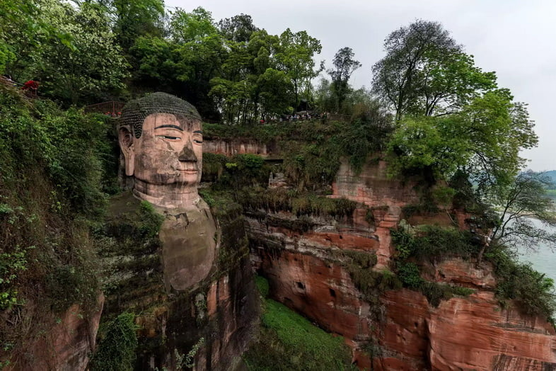 Гигантский Будда, высеченный в скале, установлен в лесу