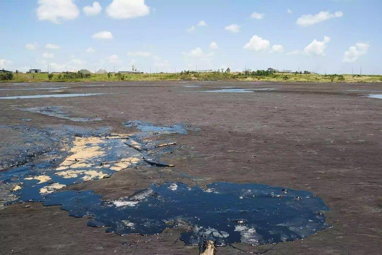 Бассейн с черной смолой или асфальтом на темно-коричневом дне озера