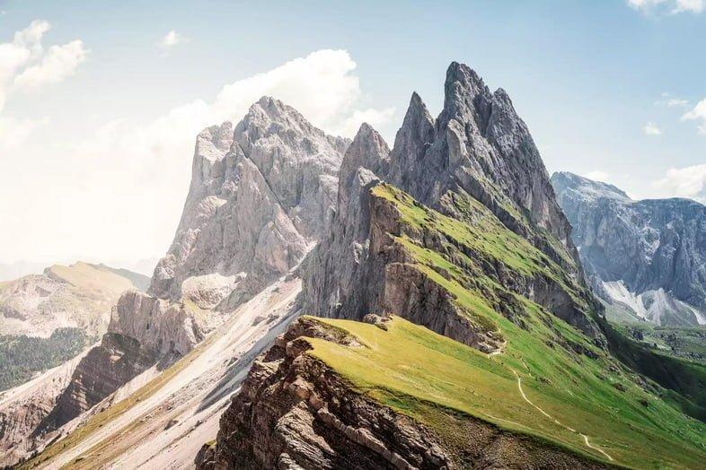 Зубчатый горный хребет с зеленым полем с одной стороны