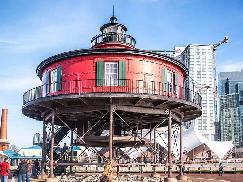 Красный маяк Семифутового холма находится во Внутренней гавани Балтимора в частично пасмурный день.