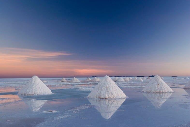 Треугольные соляные груды на соляной равнине Уюни, отражающие восход солнца