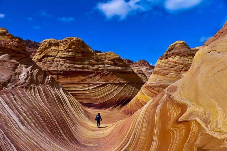 Человек идет по волнообразной скальной формации из песчаника