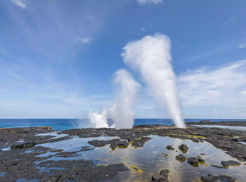 Вода выбрасывается в воздух через дыры на каменистом побережье.