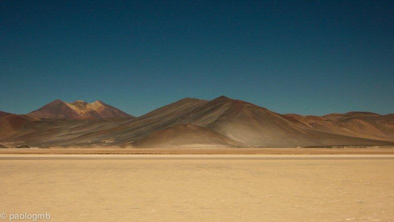 Песчаная равнина с коричневыми горами без растительности в пустыне Атакама, Чили