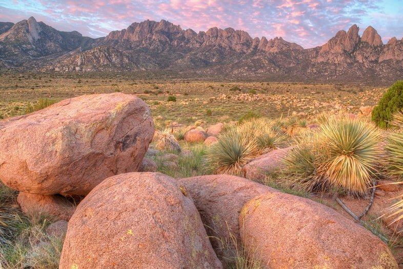 Розово-оранжевые валуны на фоне скалистых горных вершин на Национальной тропе отдыха Сьерра-Виста, Нью-Мексико