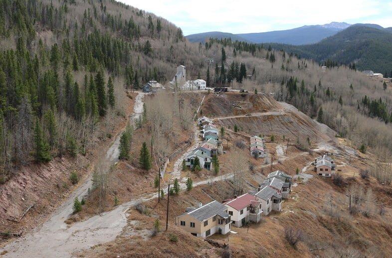 Небольшой поселок из домов и построек на крутом склоне холма