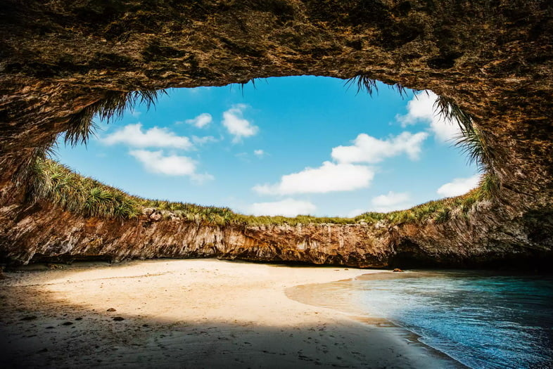 Песчаная морская пещера с круглым отверстием и видом на голубое небо.