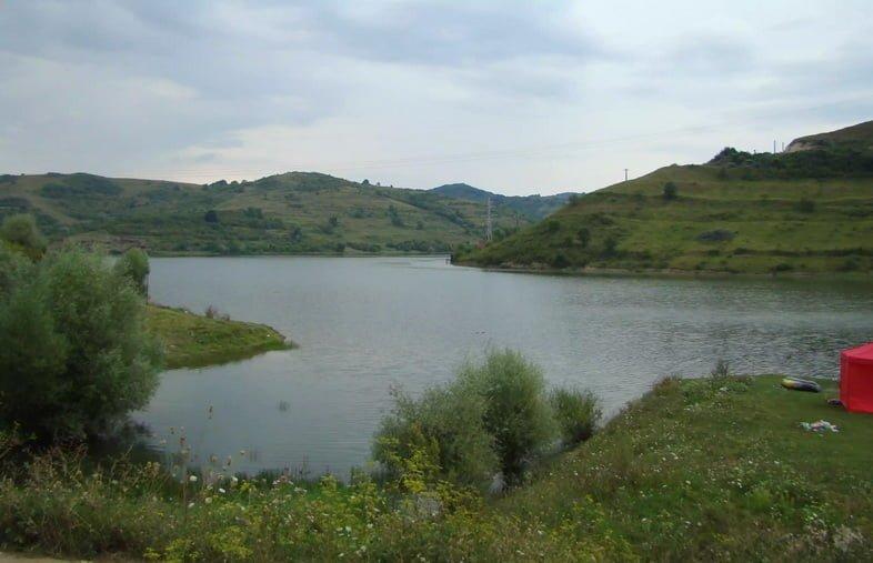 Большое озеро, окруженное холмами и зеленью.