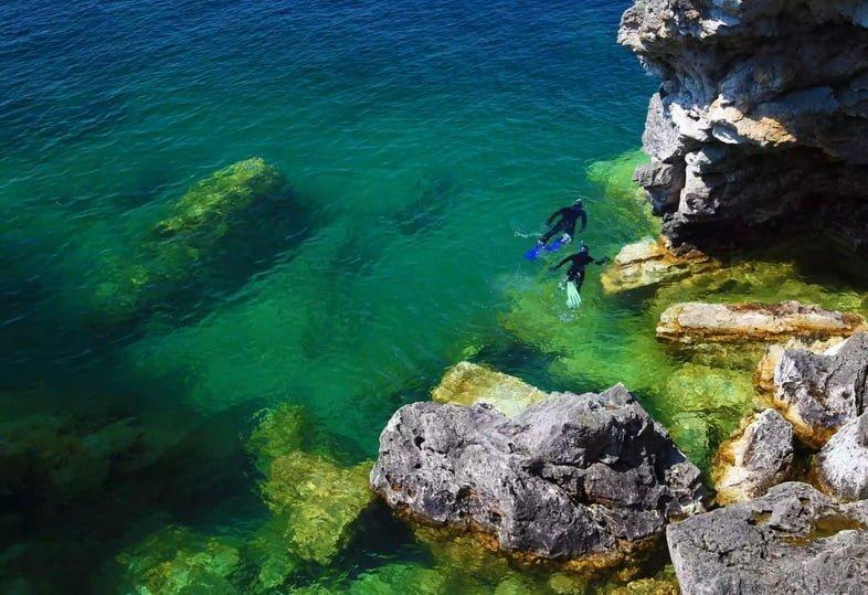 Аквалангисты исследуют скалистое озеро.