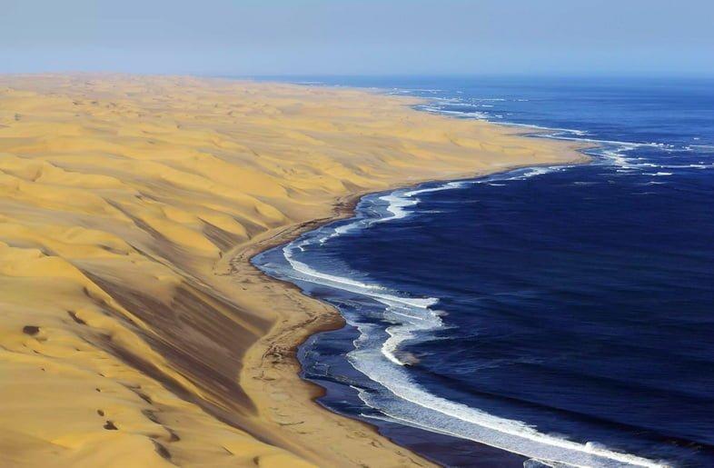 Бесплодные дюны пустыни Намиб рядом с темно-синими прибрежными водами Атлантического океана