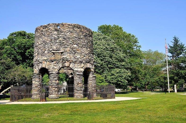 Круглая каменная башня посреди травянистого парка.