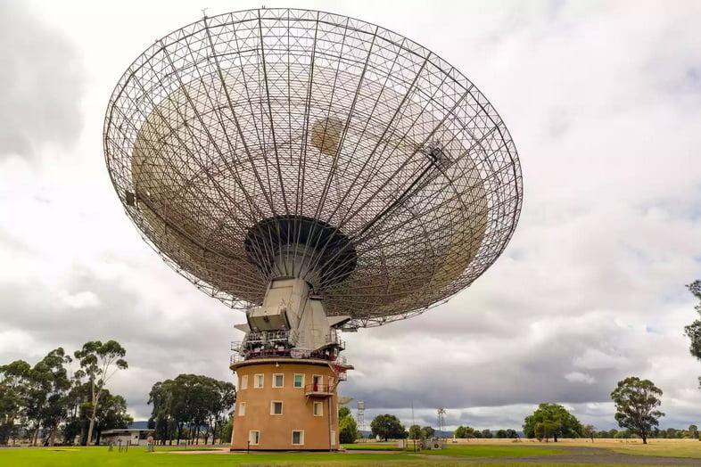 Второй по величине радиотелескоп в Южном полушарии находится на вершине круглой обсерватории Паркса в пасмурный день.