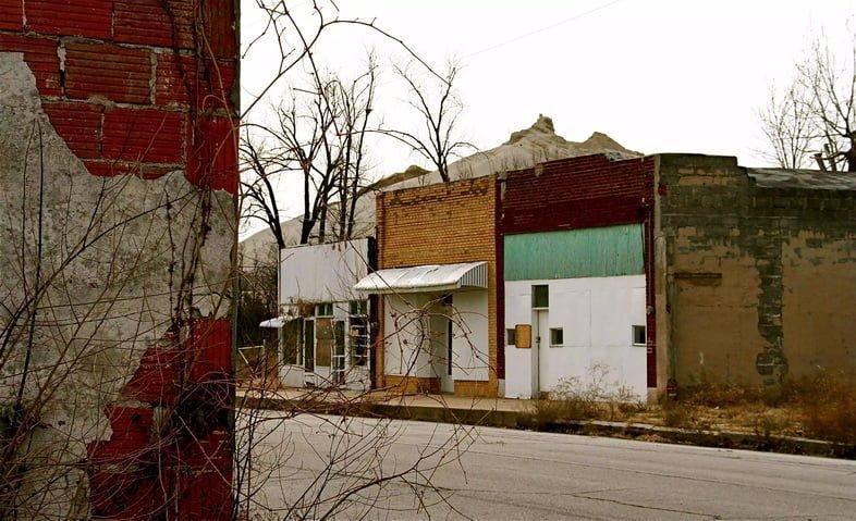 Улица с заброшенными витринами и насыпью, образовавшейся в результате горнодобывающей деятельности, на заднем плане.