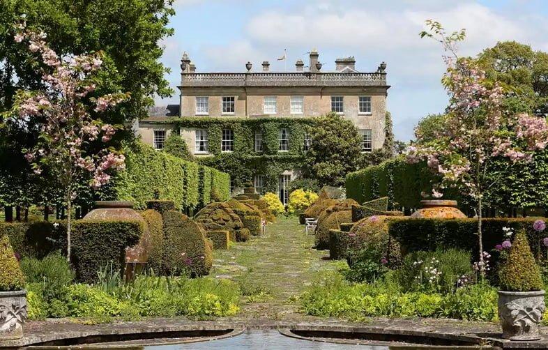 Вид на классические английские сады в Хайгроув принца Чарльза – два розовоцветущих дерева по бокам входа, за которыми следуют разнообразные аккуратно вырезанные зеленые изгороди, ведущие к собственности