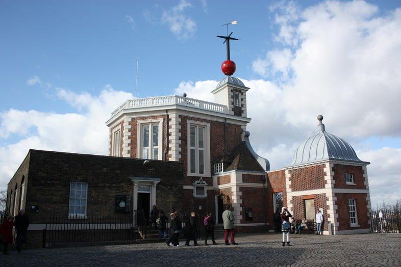 Туристы собираются возле Гринвичской королевской обсерватории в Англии.