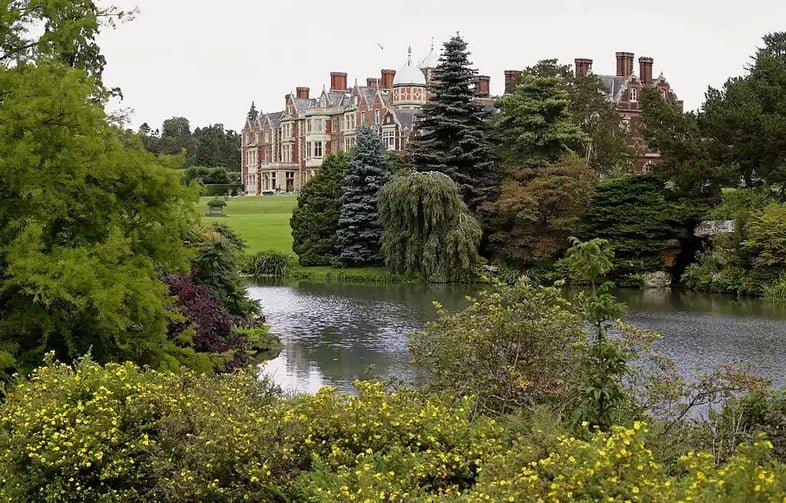 Пышные зеленые и цветущие растения, окружающие небольшой водоем перед королевским поместьем – Сандрингемским дворцом.