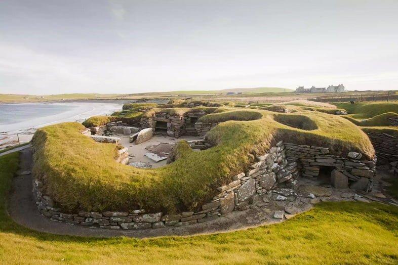 Каменное поселение, покрытое травой, на побережье Шотландии
