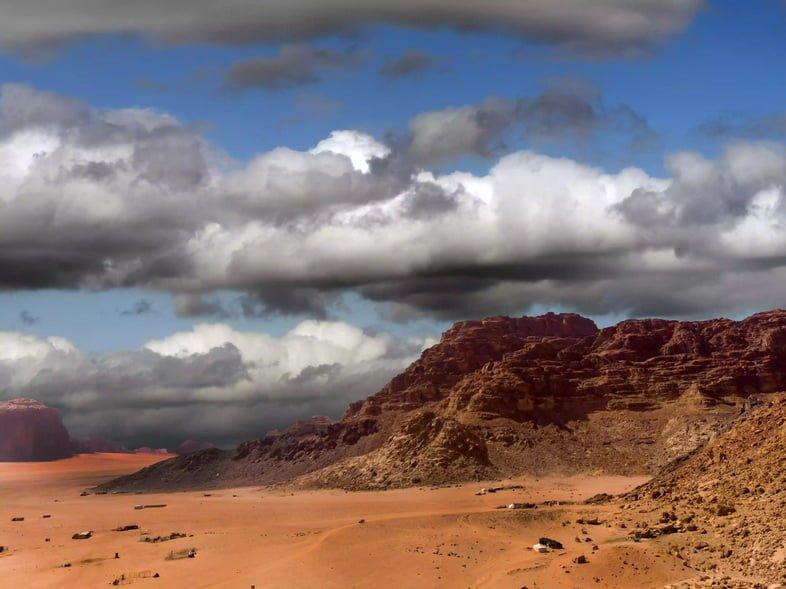 Красные пески Вади-Рам в Иордании с бесплодными скалистыми горами и грозовыми облаками на заднем плане