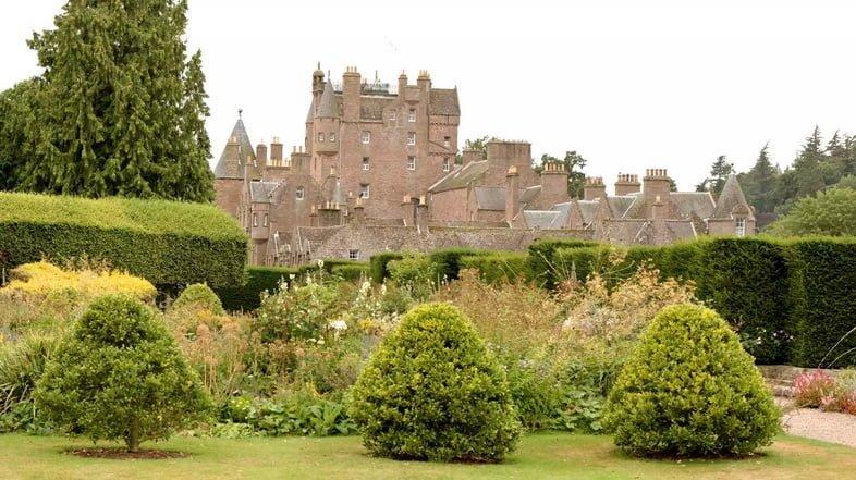 Три зеленые скульптурные изгороди перед более высокими цветущими растениями и более крупные зеленые изгороди на обширной зеленой лужайке, ведущей к замку Глэмис.