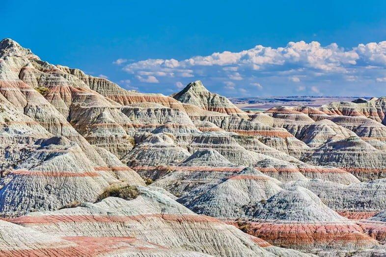 Каменистая местность с чередующимися красными и серыми полосами на фоне голубого неба.
