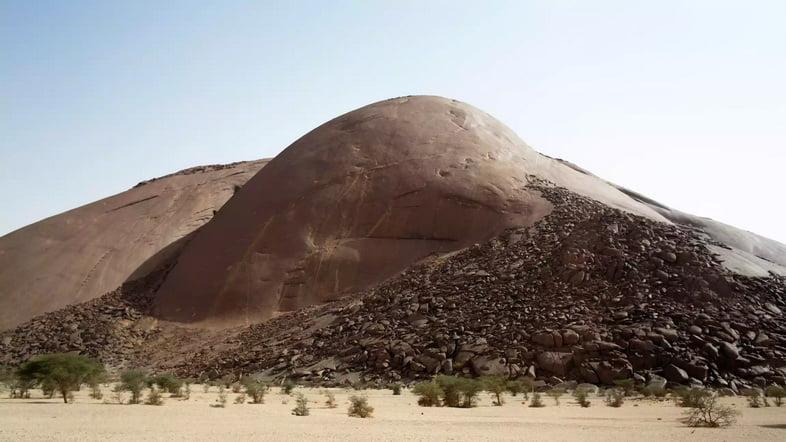 Округлый каменный монолит в пустынном пейзаже
