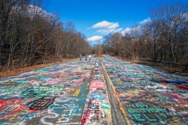 Три человека идут по дороге, покрытой граффити