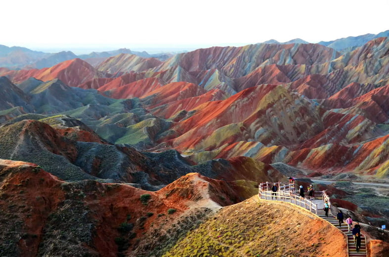 Туристы на тропе смотрят на пейзаж с полосатыми красными, синими и желтыми горами.