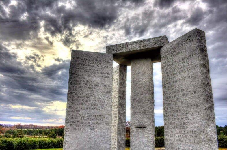 Высокие гранитные монументы с надписями на закате
