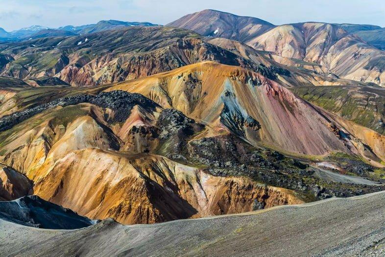 Обширный вид на горный хребет с оттенками оранжевого, синего, красного и серого.
