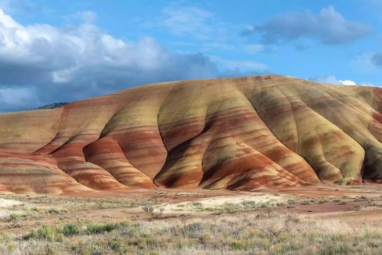 Холм в высокой пустыне Орегона с желтыми и красными полосами